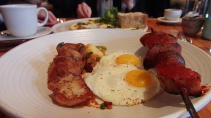 Brochette de Porc - Barbequed bacon, mortadella, spicy andouille, saucisson de Paris, fried eggs, tomatillo & pineapple salsa, spiced potatoes